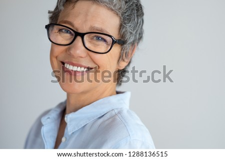 50aeec6ad0a Portrait of senior woman with eyeglasses looking at camera isolated on gray  background. Cheerful mature