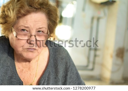 Portrait of senior woman with glasses looking at photographer while taking a picture. the woman has short blond hair. #1278200977