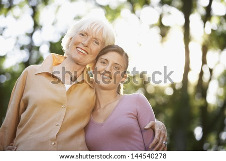Portrait of senior woman with granddaughter smiling together in park