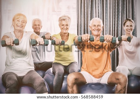 Portrait of seniors using exercise ball and weights during sports class