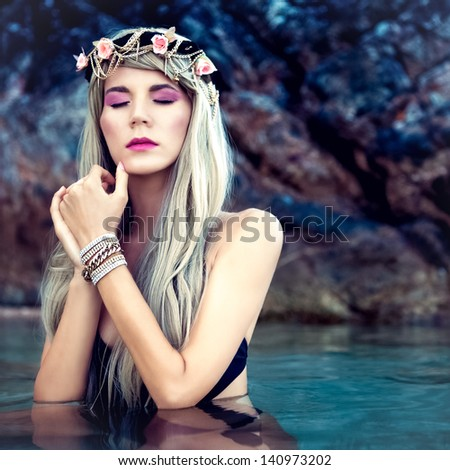 Portrait of sensual blond girl in a wreath in the sea