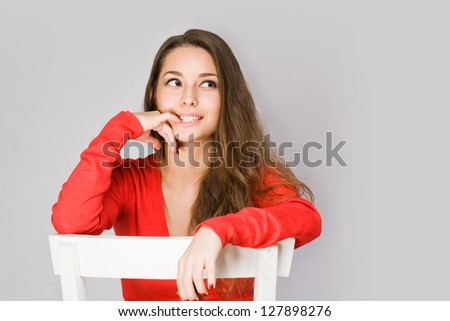 Portrait of sensual happy young brunette woman in red sweater.