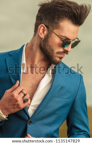 portrait of sensual man with sunglasses holding suit collar and looking down to side while standing outside on field, on cloudy weather