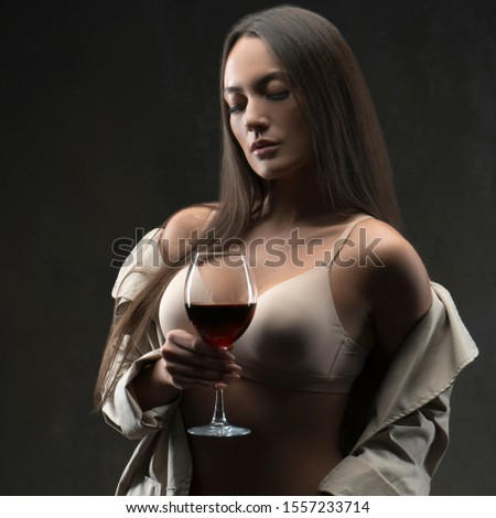 portrait of sensual woman with red wine glass in hands, wearing skin tone comfort lingerie and coat. Dark background