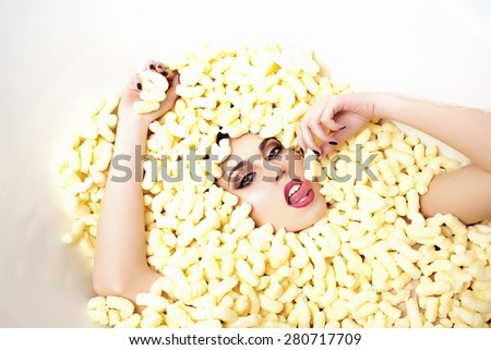 Portrait of sensual young beautiful girl face in corn sticks heap in bathtub with raised hands tasting and  looking forward lying on light food background copy space, horizontal picture