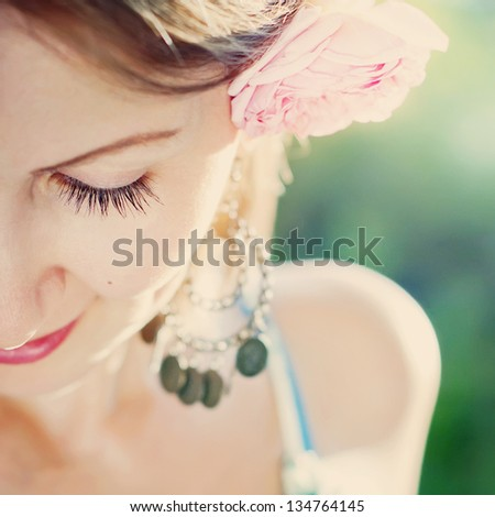 Portrait of Sensual Young Beautiful Woman with pink rose in her hair on a green background - stock photo