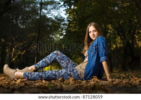 Portrait of sensual young woman posing at autumn forest