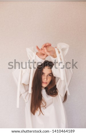 Portrait of sensuality freedom woman. Girl wears white or milky shirt. Fashionable details wide sleeves with long tapes. Details of everyday elegant look. Model wearing casual outfit. #1410464189