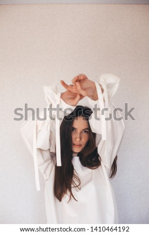 Portrait of sensuality freedom woman. Girl wears white or milky shirt. Fashionable details wide sleeves with long tapes. Details of everyday elegant look. Model wearing casual outfit. #1410464192