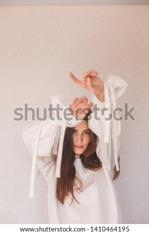 Portrait of sensuality freedom woman. Girl wears white or milky shirt. Fashionable details wide sleeves with long tapes. Details of everyday elegant look. Model wearing casual outfit. #1410464195