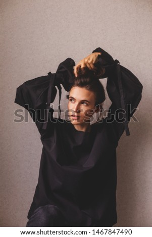 Portrait of sensuality woman making high bun and look at side. Girl wears black shirt. Fashionable details wide sleeves with long tapes. Details of everyday elegant look. Model wearing casual outfit.