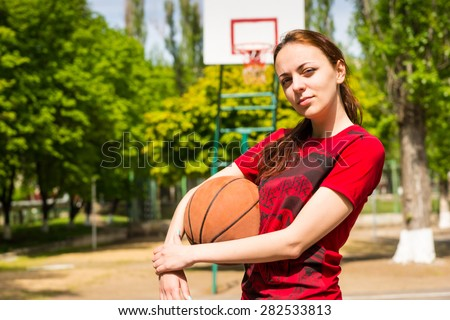 Portrait of Serious and Confident Young Woman Wearing Red T-Shirt Holding Basketball on Outdoor Court