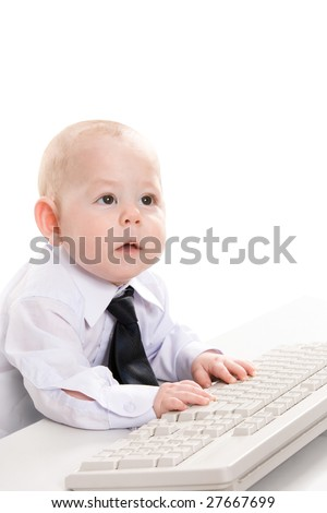 Portrait of serious baby boy typing on keyboard and looking aside