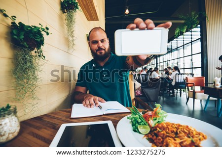 Portrait of serious bearded male food blogger holding smartphone for making picture of meal and interior of restaurant, serious writer sitting with notepad in cafe for creating review of cuisine
