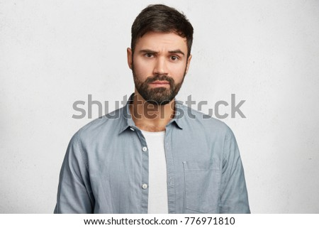 Portrait of serious bearded male wears fashionable denim shirt, hears attentively something important, isolated over white concrete wall. Young male student with thick beard and mustache indoor #776971810