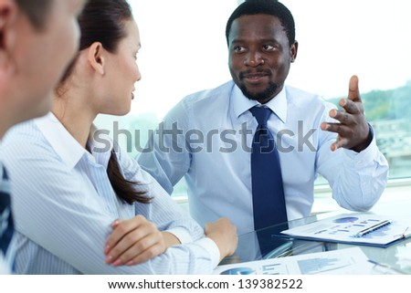 Portrait of serious boss talking to his employees at meeting
