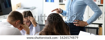 Portrait of serious boss woman in classic shirt pointing finger and giving important directions to colleagues. Upset biz team sitting at table with heads down. Teamwork and teambuilding concept