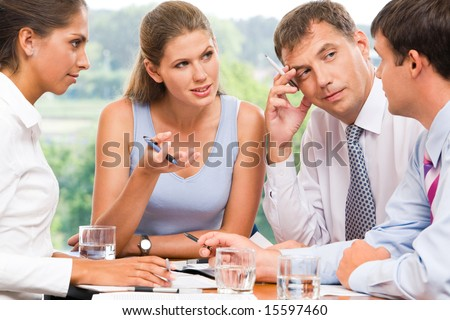 Portrait of serious business partners looking at man explaining new idea and listening to him