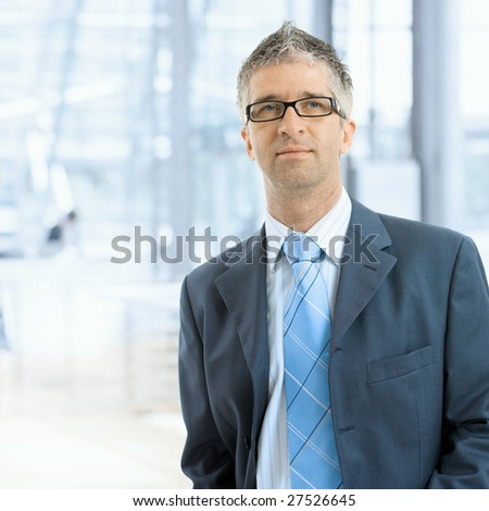 Portrait of serious businessman wearing gray suit with blue tie and glasses, standing in office lobby, in front of windows.