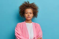 Portrait of serious dark skinned woman with combed curly bushy hair has natural beauty looks directly at camera wears pink jumper isolated on blue background. Human face expressions concept.