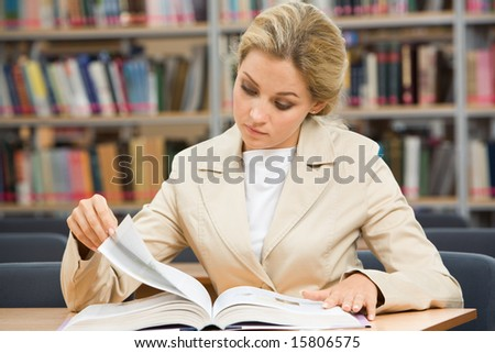 Portrait of serious female leaning over book in the library and reading it - stock photo