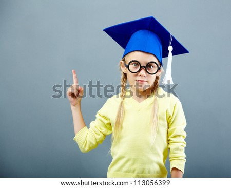 Portrait of serious girl in eyeglasses pointing upwards and looking at camera