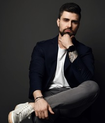 Portrait of serious handsome brutal man in stylish smart casual clothes with tatoo on hand sitting, touching chin and looking at camera over dark background. Stylish business casual style for men