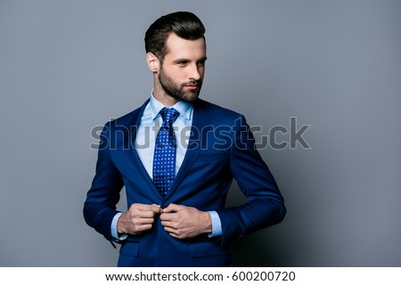 Portrait of serious handsome man in blue suit and tie buttoning jacket ストックフォト ©