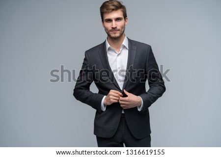 Portrait of serious handsome man in gray suit buttoning jacket against gray background. #1316619155