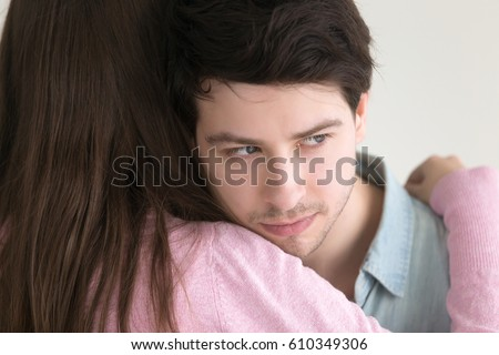 Portrait of serious liar guy hugging woman, thinking about work or imagining something else, pensive distrustful man looking away, couple embracing, cheating boyfriend in foreground.. Fake forgiveness