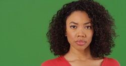 Portrait of serious looking black woman staring at camera on green screen