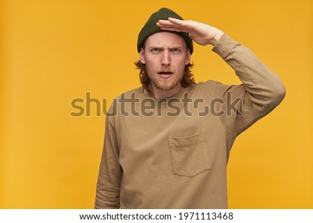 Portrait of serious male with blond hair and beard. Wearing green beanie and beige sweater. Holds palm next to forehead and gaze into distance. Watching at the camera isolated over yellow background Stock photo ©