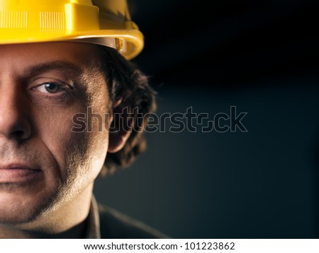 Portrait of serious middle aged man working as construction worker with hardhat. Copy space