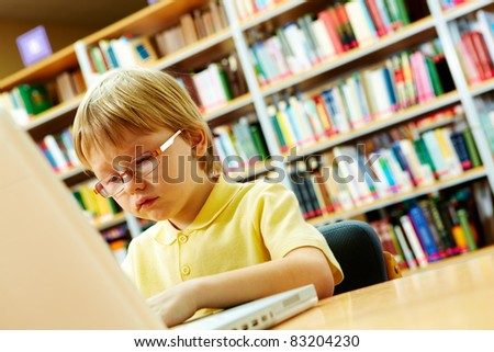 Portrait of serious schoolkid working with laptop in the library