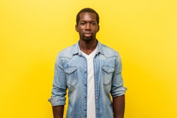 Portrait of serious self-assertive handsome man in denim casual shirt with rolled up sleeves looking smart and professional, freelancer or employee. indoor studio shot isolated on yellow background