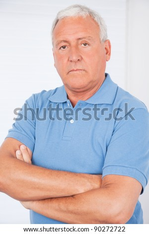 Portrait of serious senior man with arms crossed
