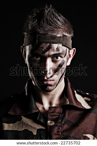 portrait of serious soldier over black background