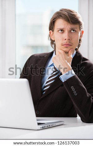 Portrait of serious thinking business man with laptop