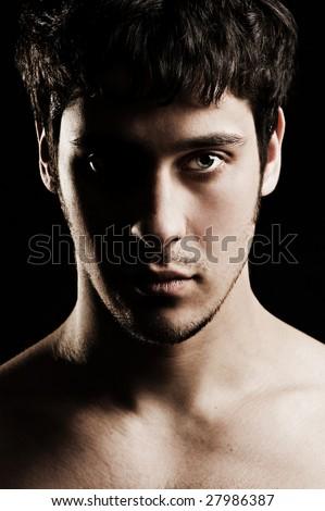 portrait of serious unshaven man against black background