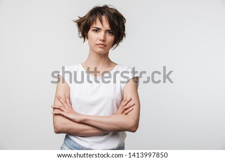 Portrait of serious woman with short brown hair in basic t-shirt frowning and looking at camera isolated over white background Сток-фото ©