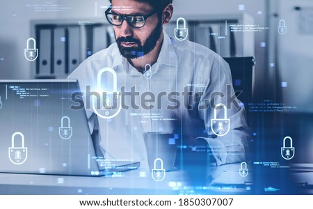 Portrait of serious young businessman in glasses working in blurry office with double exposure of immersive cyber security interface. Toned image