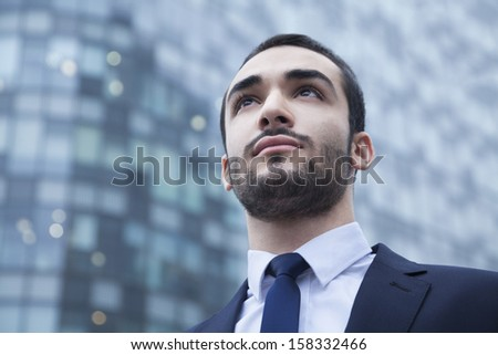 Portrait of serious young businessman looking up