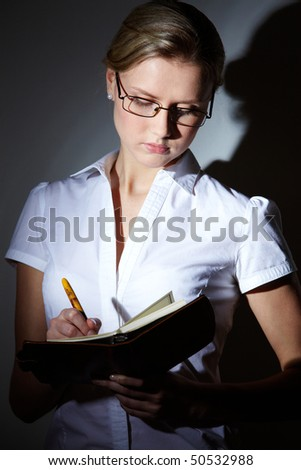 Portrait of serious young businesswoman making note in her daily notepad