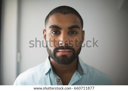 Portrait of serious young man against wall