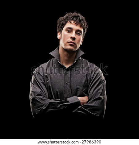 portrait of serious young man in shirt against black background