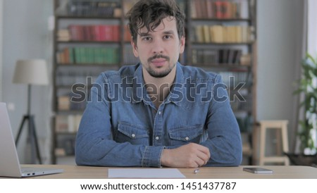 Portrait of Serious Young Man Looking at Camera in Casual Office