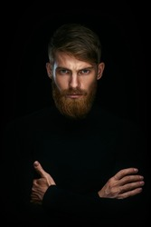 Portrait of serious young man with folded and crossing hands standing Isolated on black background and looking at camera Confident concept