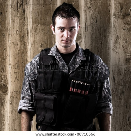 portrait of serious young soldier against a wooden wall - stock photo