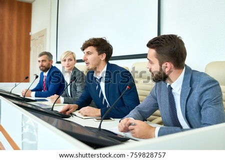 Portrait of several business people sitting in row participating in political debate during press conference answering media questions speaking to microphone #759828757