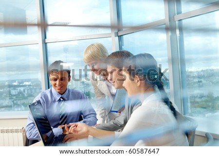 Portrait of several colleagues looking at laptop screen during meeting in office